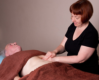 Sally Tyler showing abdominal massage at the Natural Health Consultancy